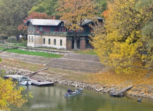 """altes Bootshaus (um 1900), am Giebel den Namen """"Spartacus"""" in Rotweiss über gekreuzten Rudern, gegenwärtig eine Baustelle"""