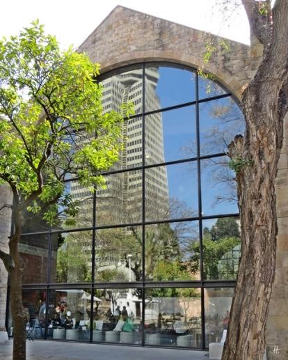 Spiegelung im Fenster vom Cafés des Marine-Museums von Barcelona in den Drassanes Reials, den mittelalterlichen Königlichen Werften. Orangenbäumchen davor.