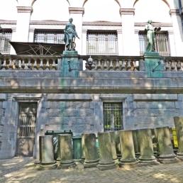 Blick auf die Balustrade der Terrasse vom Museums-Café mit den künstlerischen Figuren; unterhalb davon, die Kunst, an einem solchen Ort Mülltonnen zu verbergen.