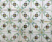 Blumenfliesen an einer Fassade - leider mit unübersehbaren Spuren von Versuchen, sie abzulösen und zu stehlen.
