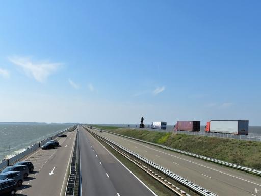 2019-04-09 NL Abschlussdeich des IJsselmeeres (5) A7 Richtung Den Oever (Nordholland) + Standbild Cornelis Lely, 1954 von Mari Andriessen gestaltet